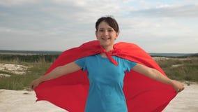 El super héroe hermoso de la muchacha corre a través de campo en capa roja delante del cielo azul y sonríe cámara lenta Sue?os de metrajes