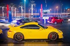 El Supercar de lujo Porsche 911 Carrera 4 GTS amarillea el color parqueado al lado de la alameda de Dubai Lamborghini es costoso  fotos de archivo libres de regalías