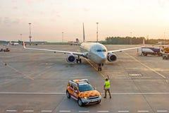 El supervisor del ordenar de la aviación resuelve el aeroplano en el aeropuerto - pulgares del pasajero para arriba El avión está imágenes de archivo libres de regalías