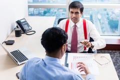 El supervisor habla con el profesional subordinado en el edificio de oficinas imagen de archivo
