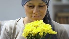 El superviviente feliz del cáncer que huele las flores, siente mejor después de la quimioterapia, esperanza almacen de video