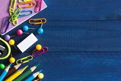 El surtido de efectos de escritorio de la escuela tales como clips de papel, pernos, cuaderno, plumas, lápices, reglas, scissors  Fotografía de archivo libre de regalías