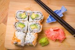 El sushi California rueda el aperitivo con el aguacate del arroz con chopstic Imagenes de archivo