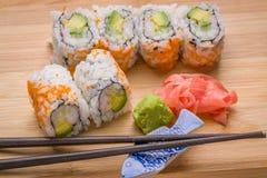 El sushi California rueda el aperitivo con el aguacate del arroz con chopstic Imágenes de archivo libres de regalías