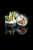 El sushi con los salmones y el aguacate en un fondo negro con reflejan Fotos de archivo