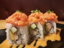 El sushi de color salmón de la fusión, la materia con el pepino, el palillo y el mango, comida del cangrejo del estilista con la  Imagen de archivo
