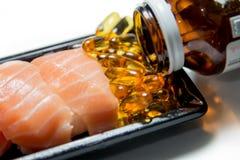 El sushi de color salmón sirvió con las píldoras del aceite de pescado vertidas de la botella marrón Fotos de archivo