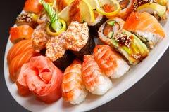 el sushi del uramaki y del nigiri sirvió en el cierre blanco de la placa para arriba Fotos de archivo
