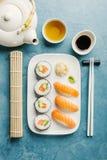 El sushi y el té sirvieron en la placa en la tabla azul Foto de archivo libre de regalías