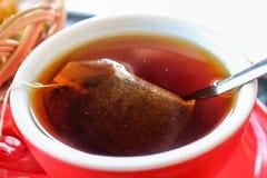 El té caliente en una taza roja imagenes de archivo