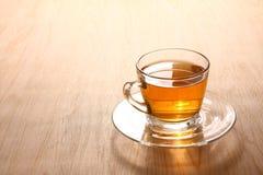 El té caliente herbario se coloca en un vidrio claro colocado en un piso de madera fotografía de archivo