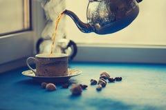 El té caliente se vierte de una caldera de acero del vintage en una taza Foto de archivo libre de regalías