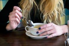 El té de la bebida de la mujer en un café y sostiene una cuchara Fotografía de archivo libre de regalías