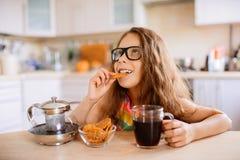 El té de la bebida de la niña y come las galletas Fotos de archivo
