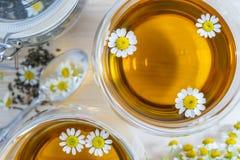 El té de manzanilla en las tazas de té de cristal se cierra para arriba en una tabla de cocina de madera imagen de archivo