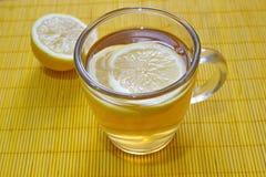 El té del limón con el limón junta las piezas en la tabla Foto de archivo