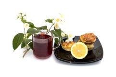 El té, el limón y los pasteles de queso en una placa las bebidas adornadas con una flor ramifican Imagen de archivo libre de regalías