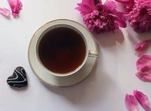 El té en una taza y una peonía hermosas florece en la tabla con una galleta bajo la forma de almuerzo caluroso del desayuno Fotos de archivo libres de regalías