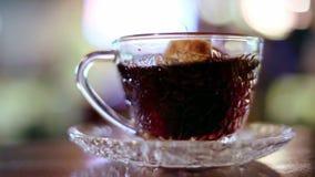 El té negro en un bolso preparó en una taza de cristal almacen de video