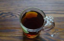 El té negro en una taza y una cereza florece por el lado derecho de la taza de té Foco selectivo Imagen de archivo libre de regalías