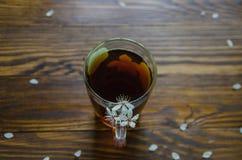 El té negro en una taza y una cereza florece por el lado derecho de la taza de té Visión superior Foco selectivo Foto de archivo libre de regalías