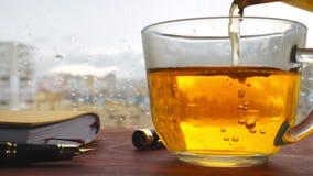 El té se vierte en una ventana que hace una pausa de la taza Día lluvioso Otoño almacen de metraje de vídeo