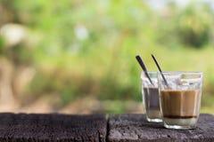 El té tailandés caliente de la leche y la bebida local de la calle de la firma caliente del cacao encendido woonden la tabla Imágenes de archivo libres de regalías