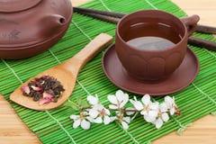 El té verde y Sakura japoneses ramifican sobre la estera Fotografía de archivo