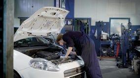 El técnico automotriz está en un taller de reparaciones del coche, capilla de apertura, encendiéndose por la linterna del bolsill almacen de video