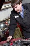El técnico automotriz trabaja debajo de la capilla del coche en la reparación auto Imagen de archivo libre de regalías