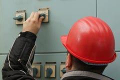 El técnico con el casco rojo apaga el interruptor fotos de archivo libres de regalías