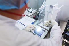 El técnico de laboratorio en guantes de goma estéril, pesa las tabletas manufacturadas en las escalas del control Foto de archivo