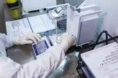 El técnico de laboratorio en guantes de goma estéril, pesa las tabletas manufacturadas en las escalas del control fotos de archivo