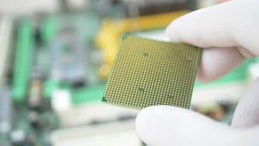 El técnico de laboratorio en los guantes y la capa blancos del laboratorio guarda el procesador de la CPU del ordenador metrajes