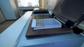 El técnico de laboratorio pone muestras de sangre en una máquina para analizar almacen de metraje de vídeo