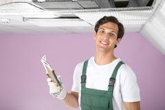 El técnico de sexo masculino con los alicates acerca al acondicionador de aire fotografía de archivo