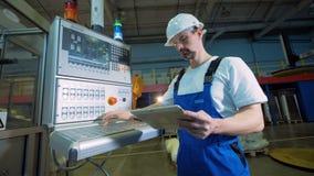 El técnico de sexo masculino con una tableta es botones que empujan en un tablero de control almacen de metraje de vídeo