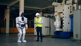 El técnico de sexo masculino está controlando los movimientos del robot almacen de video