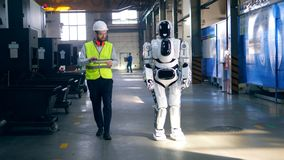 El técnico de sexo masculino está manejando un robot por la tableta almacen de metraje de vídeo