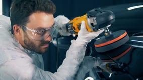 El técnico de sexo masculino está utilizando un buffwheel para esmaltar un coche negro almacen de metraje de vídeo