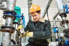 El técnico del fontanero trabaja con la bomba de agua foto de archivo