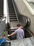 El técnico del mantenimiento hace servicio de la escalera móvil Fotos de archivo