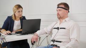 El técnico del polígrafo lee preguntas de un ordenador portátil Hombre conectado con el circuito de detector de mentira almacen de metraje de vídeo