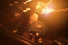 El técnico enchufa el microprocesador de la CPU a la placa madre Fotos de archivo libres de regalías
