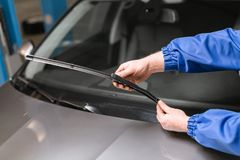 El técnico está cambiando los limpiadores de parabrisas en una estación del coche imagen de archivo libre de regalías