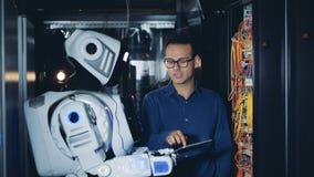 El técnico está enseñando a un robot para utilizar y para examinar los servidores del ordenador