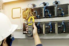 El técnico está midiendo la corriente del voltaje por Clampmeter fotografía de archivo
