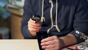 El técnico está reparando el teléfono móvil almacen de video