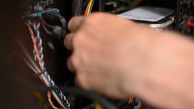 El técnico está tapando los alambres de los cables del disco duro dentro de la PC de computadora personal almacen de video