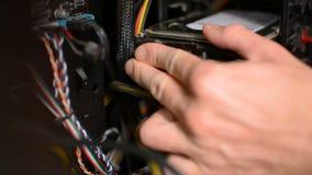 El técnico está tapando los alambres de los cables del disco duro dentro de la PC de computadora personal almacen de metraje de vídeo